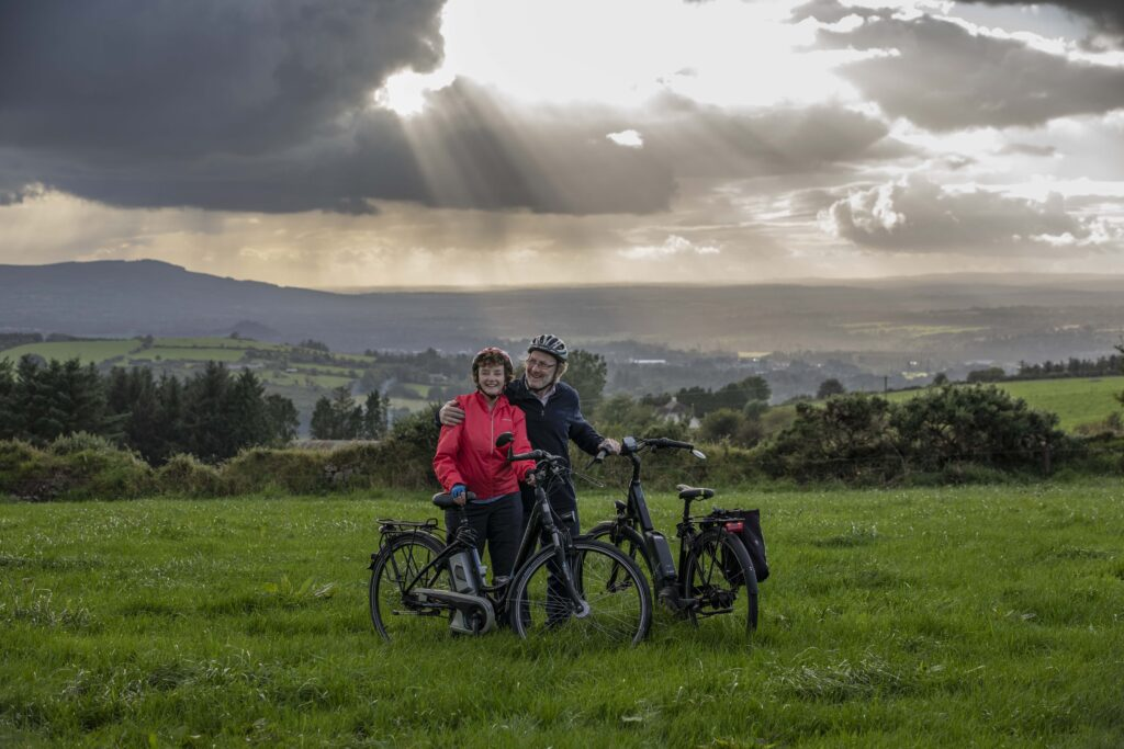 Paddy and Anna Lane of Mallow, Co. Cork in a field embracing each other and standing with their electric bicycles.