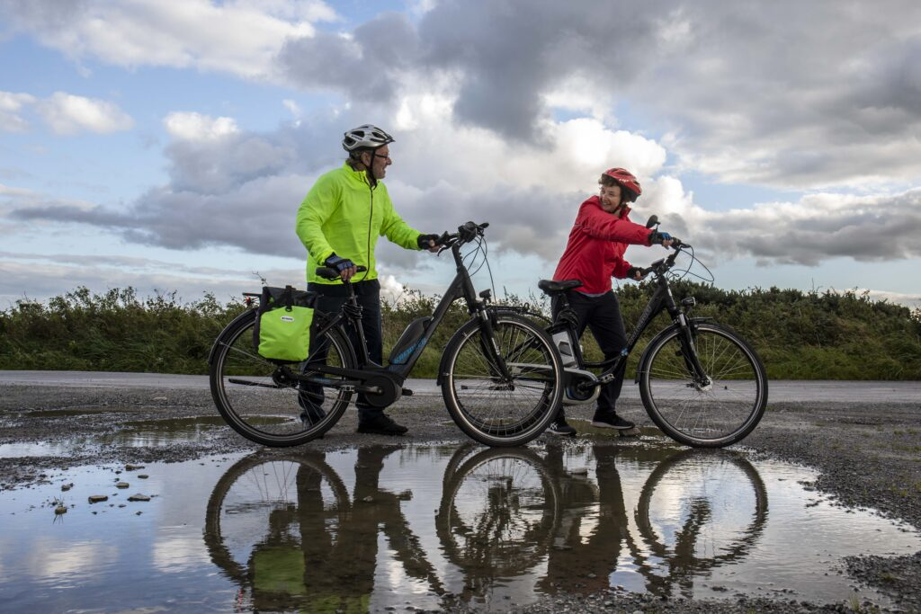 Paddy and Anna Lane of Mallow, Co. Cork looking at each other about the cycle their electric bicycles.