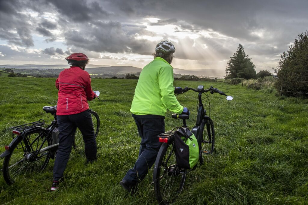 Paddy and Anna Lane of Mallow, Co. Cork walking through fields with their electric bicycles.