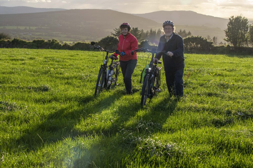 Paddy and Anna Lane of Mallow, Co. Cork walking with their electric bicycles in a field.