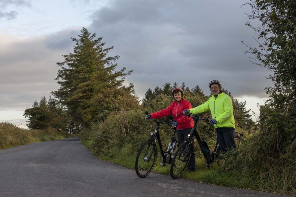 Paddy and Anna Lane of Mallow, Co. Cork exiting a field onto a country road with their electric bicycles.