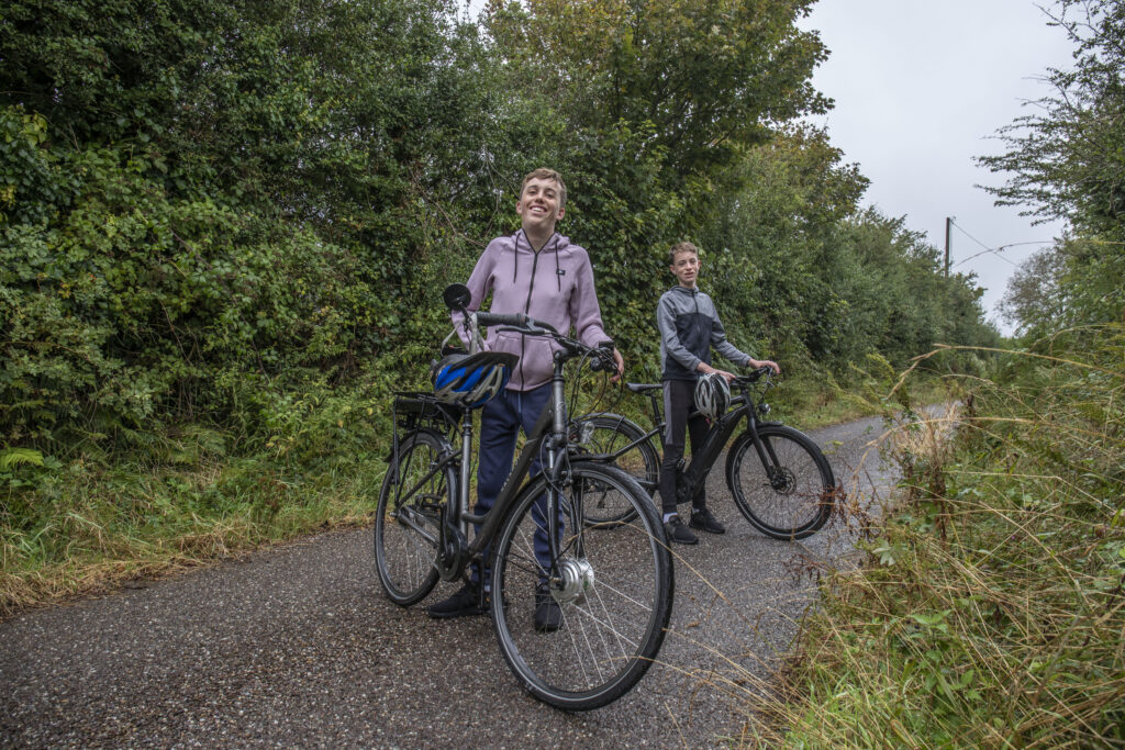 Conor O'Callaghan and his younger brother, Cormac, on a country road with their electric bicycles.