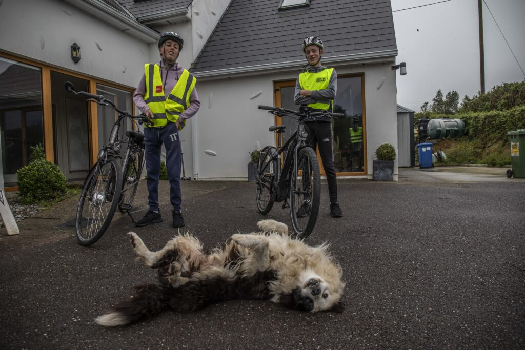 Conor O'Callaghan and his younger brother, Cormac, with their electric bicycles and a dog at their home.