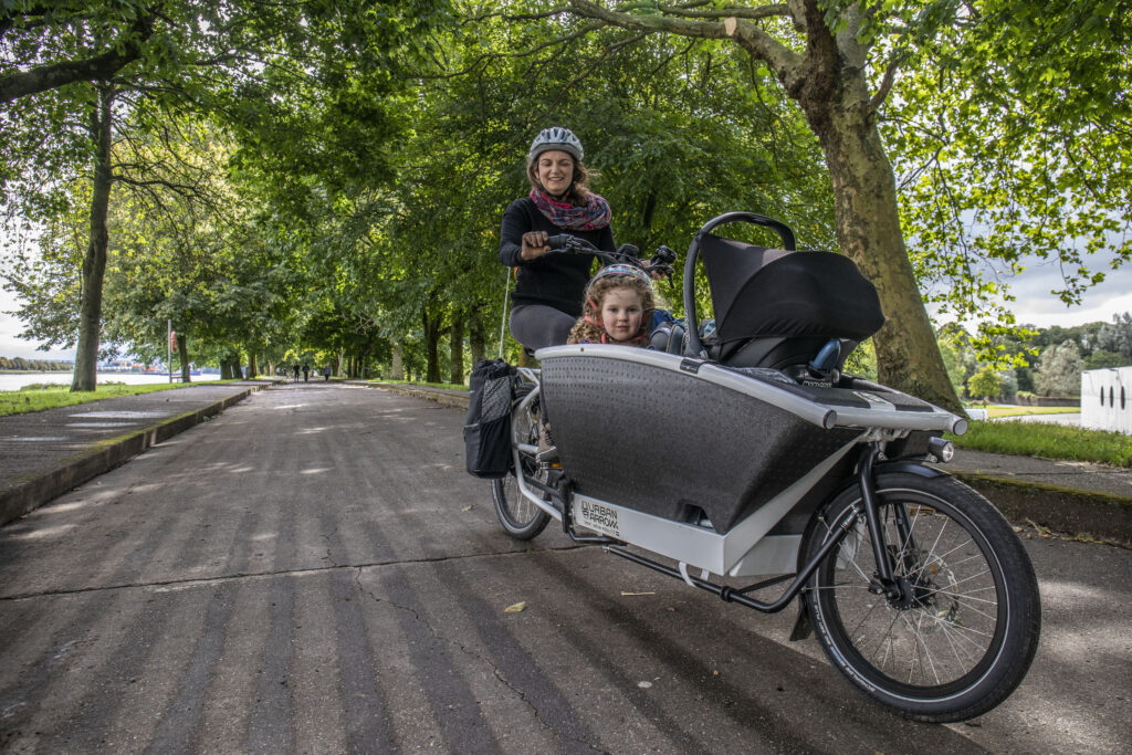 Orla Burke of Cork with her children cycling an electric cargo bicycle at the Marina in Cork.