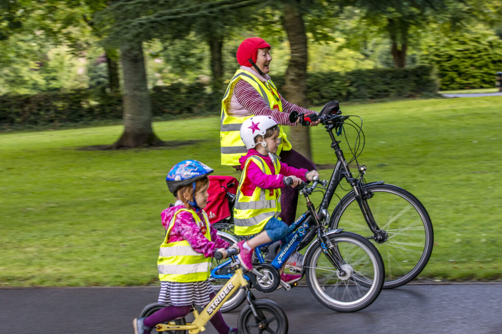 Siún Kearney of Cork cycling her electric bicyle with her grandchildren in Fitzgeral's Park.
