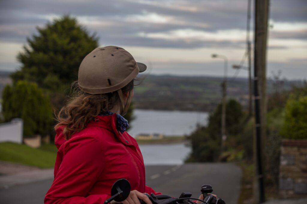Teresa Watkins of Youghal, Co. Cork with her electric bicycle looking down a road towards water.