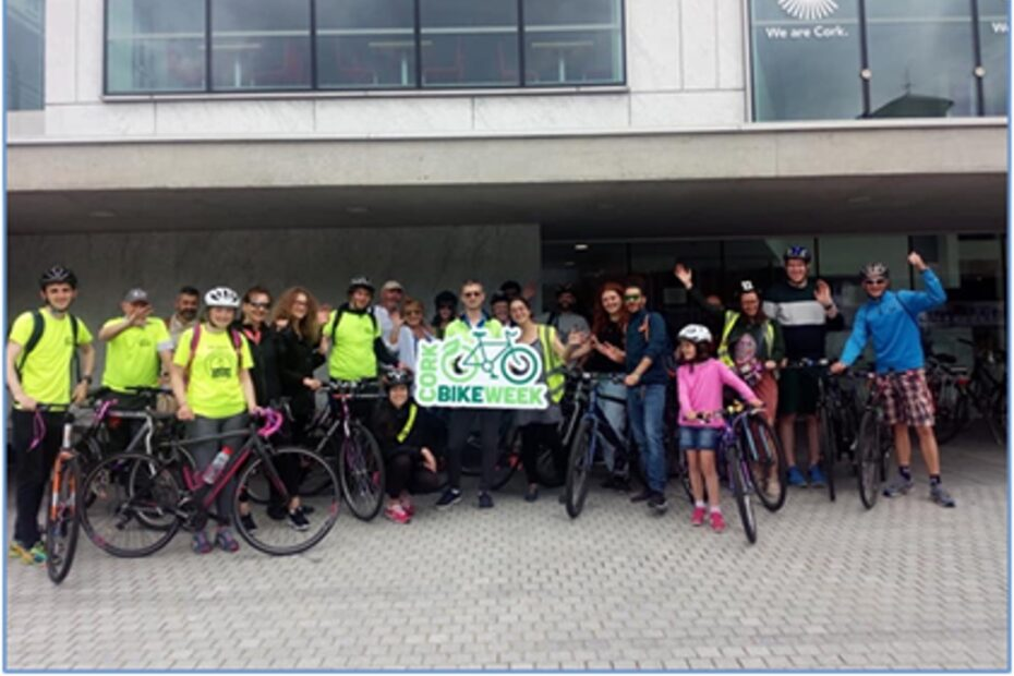 People outside Cork City Council offices holding a Bike Week banner.